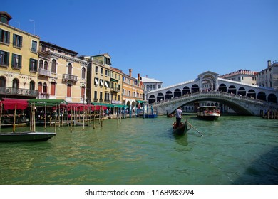 VENICE, ITALY - AUG 12, 2018 - Rialto bridge and Gondola with tourists on the Grand Canal Venice, Italy