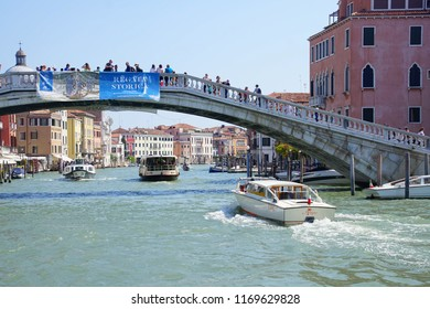 VENICE, ITALY - AUG 12, 2018 - Vaporetto transit boat passing under a bridge on the Grand Canal of Venice, Italy