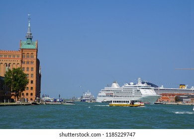 VENICE, ITALY - AUG 12, 2018 - Water taxis move past cruise ships at anchor in Venice, Italy