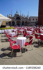 VENICE, ITALY - AUG 12, 2018 - Red restaurant chairs in the Piazza San Marco in Venice, Italy