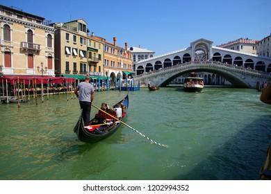 VENICE, ITALY - AUG 12, 2018 - Rialto bridge and Gondola with tourists on the Grand Canal Venice, Italy