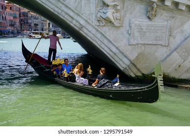 VENICE, ITALY - AUG 12, 2018 - Gondola with tourists pass under the Rialto Bridge  on the Grand Canal Venice, Italy