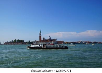 VENICE, ITALY - AUG 12, 2018 - Vaporetto transit boat in lagoon harbor of Venice, Italy
