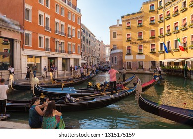 VENICE, ITALY - AUGUST 18, 2018: Gondolas with gondoliers and tourists floating on venetian canal inside the city center. Cruise on traditional boat with travellers. Famous venetian boats with people