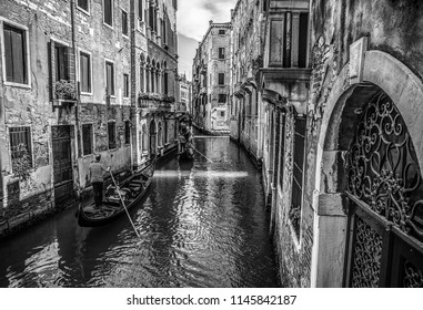 VENICE, ITALY - AUGUST 19, 2016: Traditional gondolas on narrow canal. Black-white photo on August 19, 2016 in Venice, Italy.