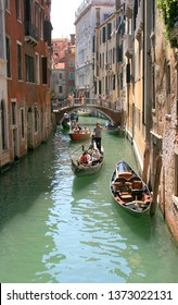 VENICE, ITALY - AUGUST 22, 2008: Gondoliers with passenger tourists float on gondolas along a narrow channel under the bridge