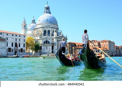 Venice, Italy - August 27, 2016: Gondoliers sail on gondolas full of tourists near Basilica Santa Maria della Salute