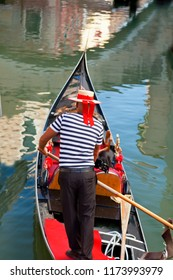 VENICE, ITALY - August 27, 2018: Gondolier rides gondola on the canals. Gondola - is one of the symbols of Venice and major mode of touristic transport