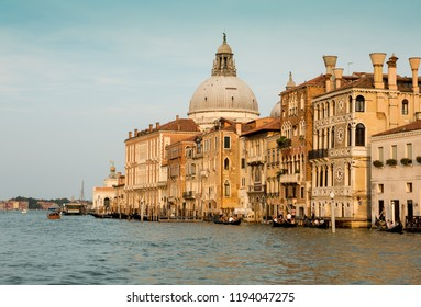 VENICE, ITALY - AUGUST 7, 2018: Venetian landscape with historic architecture among Grand Canal near The Basilica Santa Maria Della Salute. Gold sunset light.