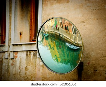Venice (Italy) Canal and embankment reflected in street mirror.