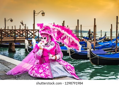 Venice, Italy, Carnival of Venice, beautiful mask at Piazza San Marco with gondolas and Grand Canal.