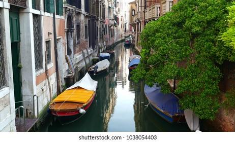 VENICE, ITALY - CIRCA JULY 2015: Empty Venice canal with boats moored near the building walls. Venice, Italy.