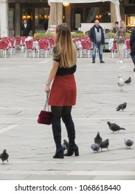 VENICE, ITALY - CIRCA MARCH 2018: unidentified stylish young woman with pigeons in Piazza San Marco (meaning St Mark square)