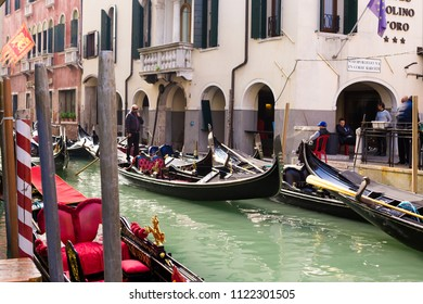 VENICE, ITALY - CIRCA OCT 2017: Canal with traditional gondola. Venetian gondolier punting gondola through green canal waters.