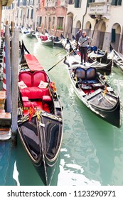 VENICE, ITALY - CIRCA OCT 2017: Gondolier sails on a gondola boat at canal with clean water. Venetian gondolier, famous entertainment.