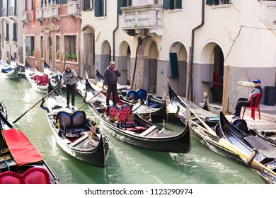 VENICE, ITALY - CIRCA OCT 2017: Gondolas and gondoliers at canal street. Venetian gondolier punting gondola through green canal waters.