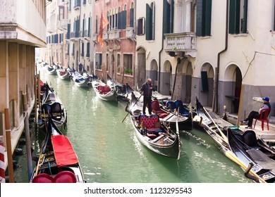 VENICE, ITALY - CIRCA OCT 2017: Vinice street with gondolier on gondola floats along the canal. Venetian gondolier, famous entertainment.