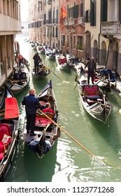 VENICE, ITALY - CIRCA OCT 2017: Venice gondola entertainment. Gondoliers make excursion for tourists through the channel in gondola.
