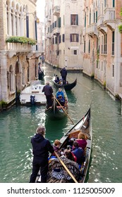 VENICE, ITALY - CIRCA OCT 2017: Venice gondola entertainment. Gondoliers makes excursion for tourists through the channel, a lot of boats in channel.