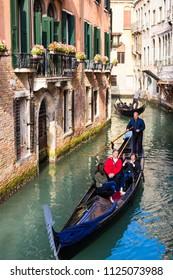 VENICE, ITALY - CIRCA OCT 2017: Venice gondola entertainment. Gondolier makes excursion for tourists through the channel.