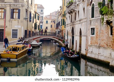 VENICE, ITALY - CIRCA OCT 2017: Venice gondola, bridge over canal, tourists walking. Gondolier makes excursion for tourists through the channel, ancient Venice architecture.
