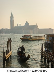 Venice, Italy - December 4 2018: Gondolier and gondola entering the Venetian Lagoon on a hazy winter's day with the Church of San Giorgio Maggiore in the background