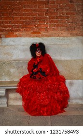 Venice, Italy - Feb 9th 2013: Woman in beautiful red dress with a mask disguised during the traditional Carnival in Venice, Italy. Venetian Carnival tradition is most famous for its distinctive masks.