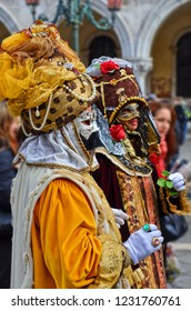 Venice, Italy - Feb 9th 2013: Two men disguised in beautiful colorful dresses with masks posing in the crowds of tourists during the traditional Carnival of Venice in Italy.