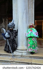 Venice, Italy - Feb 9th 2013: Couple disguised in beautiful dresses with masks and hats during the Carnival in Venice, Italy. The Venetian carnival tradition is most famous for its distinctive masks.