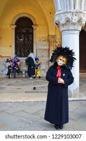 Venice, Italy - Febr 10th 2013: Disguised lady in a black dress with a colorful mask during the Carnival of Venice in Italy. Another people with masks and costumes sitting on a bench in the background