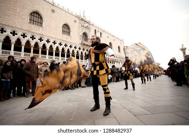Venice, Italy - February 10, 2012: men in colorful historic costumes wave flages in front of the palace of the Doge during the opening event of carnival