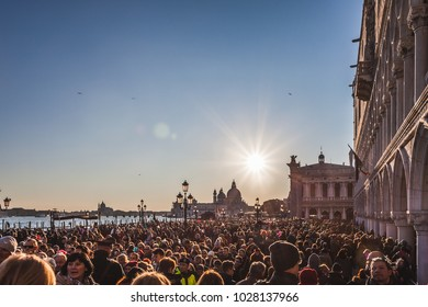 VENICE, ITALY - FEBRUARY 10 2018: Crowd towards San Marco Square, with Salute Church background. During the carnival the city is stormed by tourists