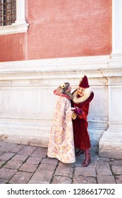Venice, Italy - February 10, 2018: Couple in white and red velvet costumes with Elizabethan collars and hats and painted faces on the street during the Carnival