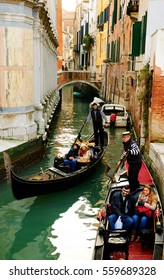 VENICE, ITALY - FEBRUARY 14, 2015: Busy gondola traffic at narrow canals during the Carnival. There are more than 400 gondolas in service in Venice.