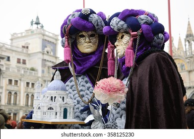 VENICE, ITALY - FEBRUARY 16, 2015: Two masks in turbans at St Mark's Square during traditional Carnival. Carnival is annual event which ends on Shrove Tuesday.