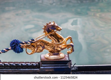 Venice, Italy- February 18, 2012: Deatil of a beautyful golden horse decorated the edge of a gondola on a Venetian canal during the Venice Carnival days.
