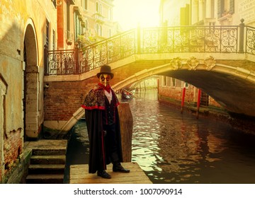 VENICE, ITALY - FEBRUARY 18, 2017: man in black costume, hat and mask in front of small bridge over narrow canal during famous traditional Carnival taking place each year on February in Venice.