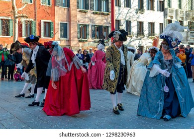 VENICE, ITALY - FEBRUARY 18, 2017: Group of people wearing typical costumes and masks dancing on small square during famous traditional annual carnival taking place each year in Venice, Italy.