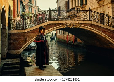 VENICE, ITALY - FEBRUARY 18, 2017: Man dressed in black costume, hat and mask  posing in front of small bridge over narrow canal during famous traditional Carnival taking place each year in Venice.