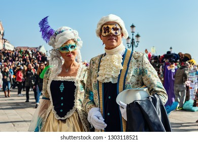 VENICE, ITALY - FEBRUARY 18, 2017: Couple of unidentified participants wear vintage colorful costumes and masks during famous traditional Carnival taking place each year on february in Venice, Italy.