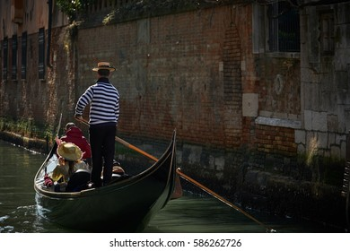 VENICE, ITALY - FEBRUARY 18, 2017: Gondoliere carries some tourists on a gondola in Venice, Italy during the Carnival holidays