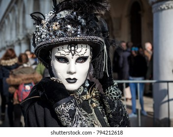 VENICE, ITALY - FEBRUARY 18, 2017: Portrait of woman in vintage black costume, gloves, hat and white mask posing on San Marco Square during famous traditional Carnival taking place each year in Venice