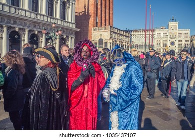 VENICE, ITALY - FEBRUARY, 2014: Amazing view on the beautiful Venice, Italy. Time of carnival. Beautiful couple of masks: red and blue during the carnival of Venice.