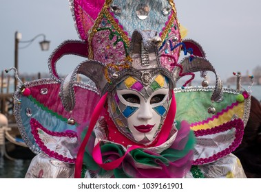 Venice Italy, February 2018. Carnival-goer in traditional costume standing with back to the Grand Canal, with gondolas in the background, during the Venice Carnival (Carnivale di Venezia)
