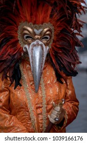 Venice Italy, February 2018. Carnival-goer wearing feathered mask and ornate costume photographed during Venice Carnival / Carnivale di Venezia.