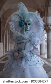 Venice Italy, February 2018. Masked woman in highly ornate white and aqua coloured costume and hat, standing under the arches at the Doges Palace during the Venice Carnival (Carnivale di Venezia)