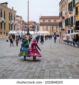 Venice, Italy, February 2018. Two women in ornate costumes and masks (the masks) walk through Campo San Stefano on their way to San Marco during the Venice carnival (Carnivale di Venezia).