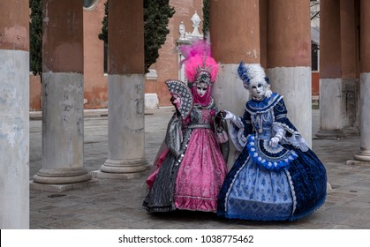 Venice Italy, February 2018. Two women in masks and ornate blue and pink costumes standing in front of pillars at a monastery during Venice Carnival (Carnivale di Venezia).