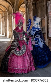 Venice Italy, February 2018. Two women in masks and ornate blue and pink costumes standing in the Rialto Market at Venice Carnival (Carnivale di Venezia)