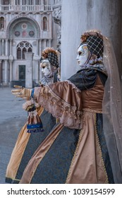 Venice Italy, February 2018. Two women in traditional costume and painted masks, standing in front of the Doges Palace and the Basilica in St Marks Square during the Venice Carnival (Carnivale)